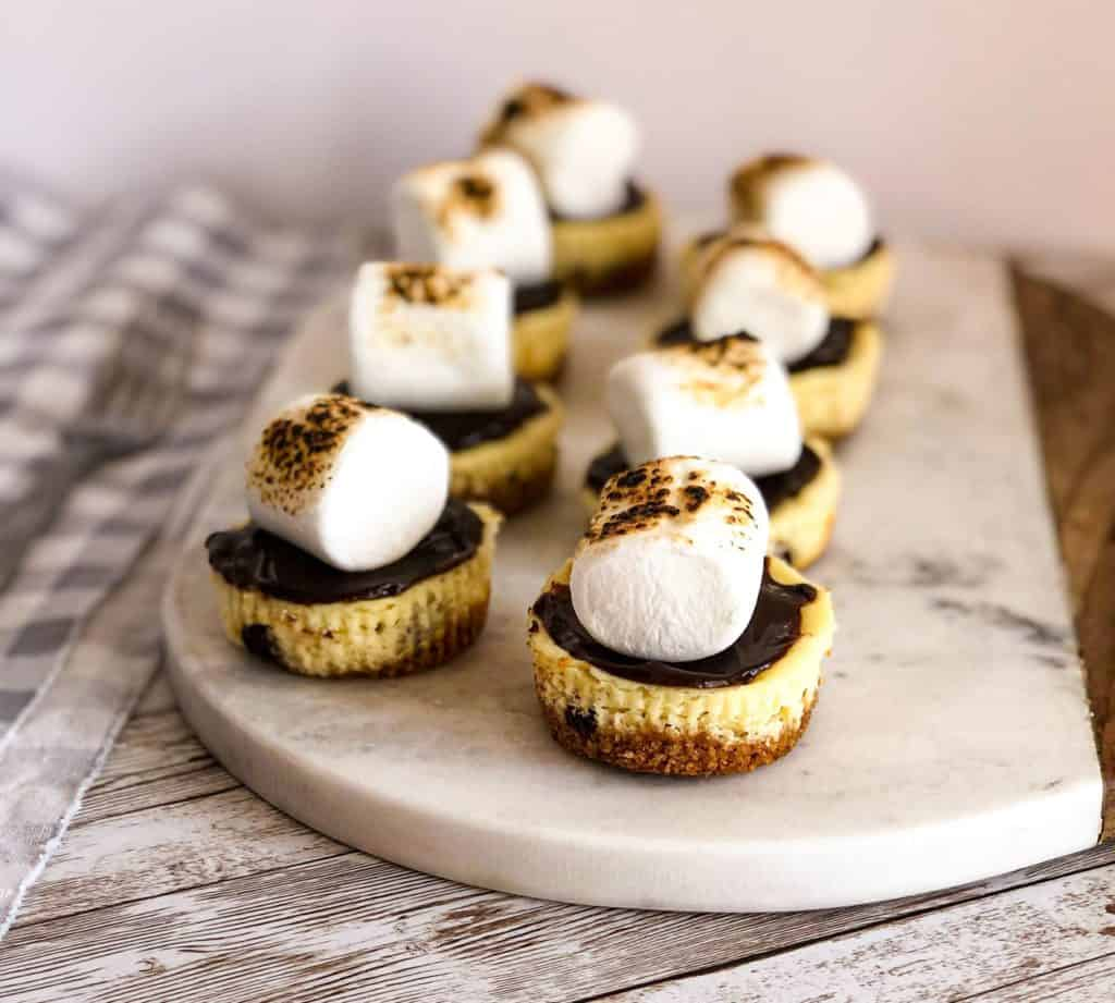 mini smores cheesecakes on a cutting board.
