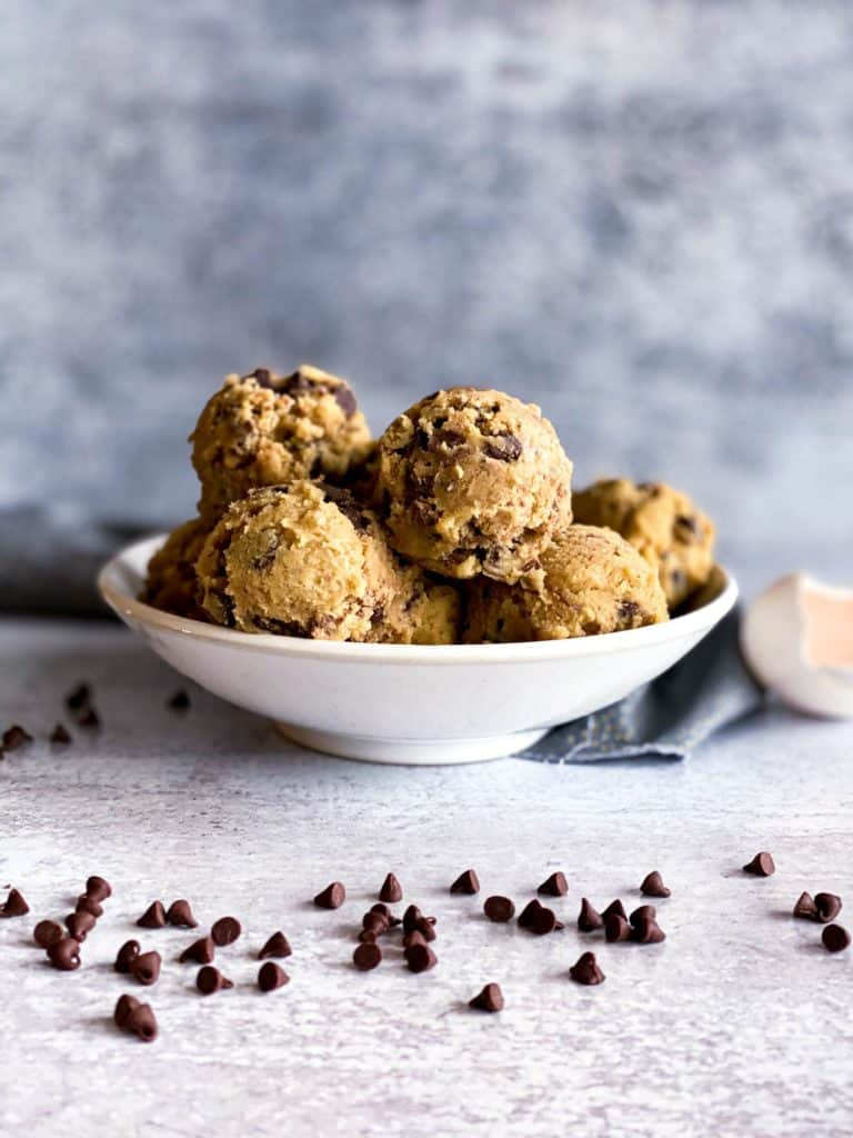 Dough balls of toffee chocolate chip cookies in a white bowl