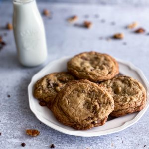 easy chewy Toffee chocolate chip cookies on a white plate with a glass of milk