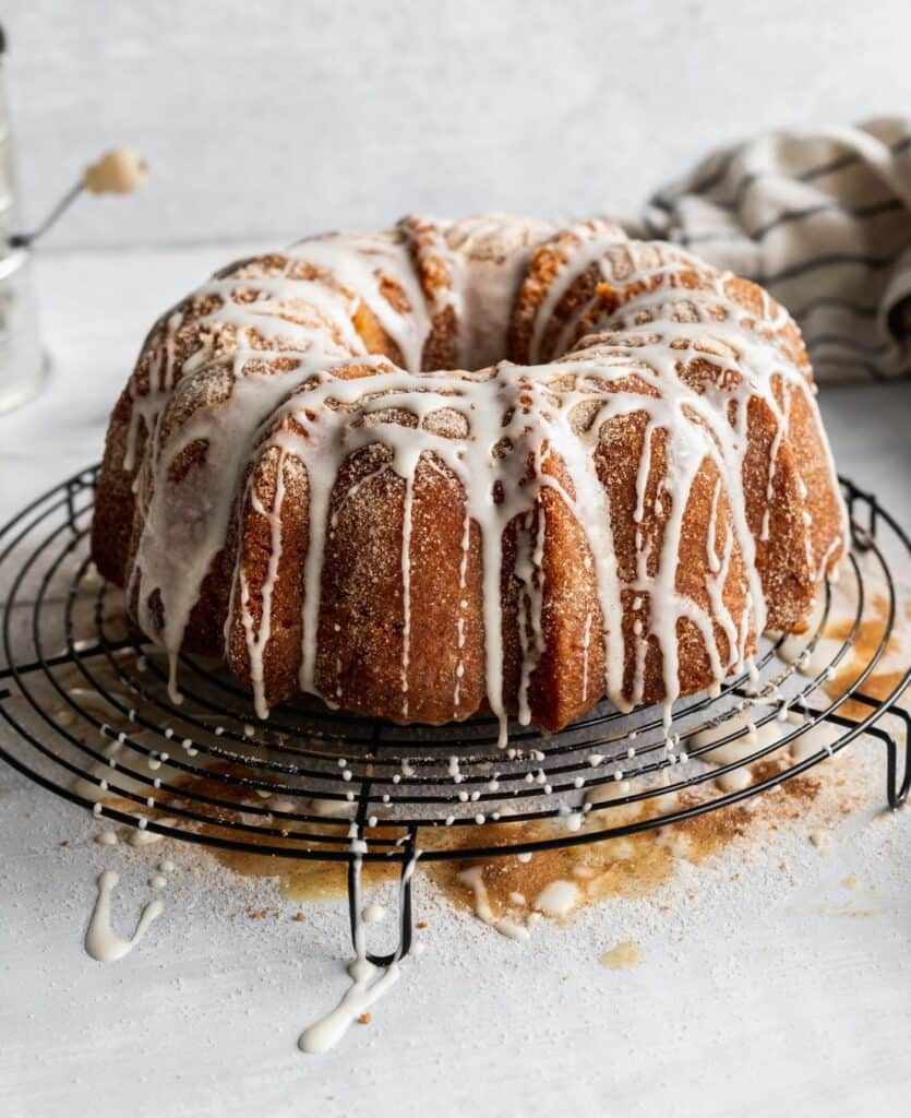 Moist apple cider donut cake on a circle cooling rack with butter and sugar all around.