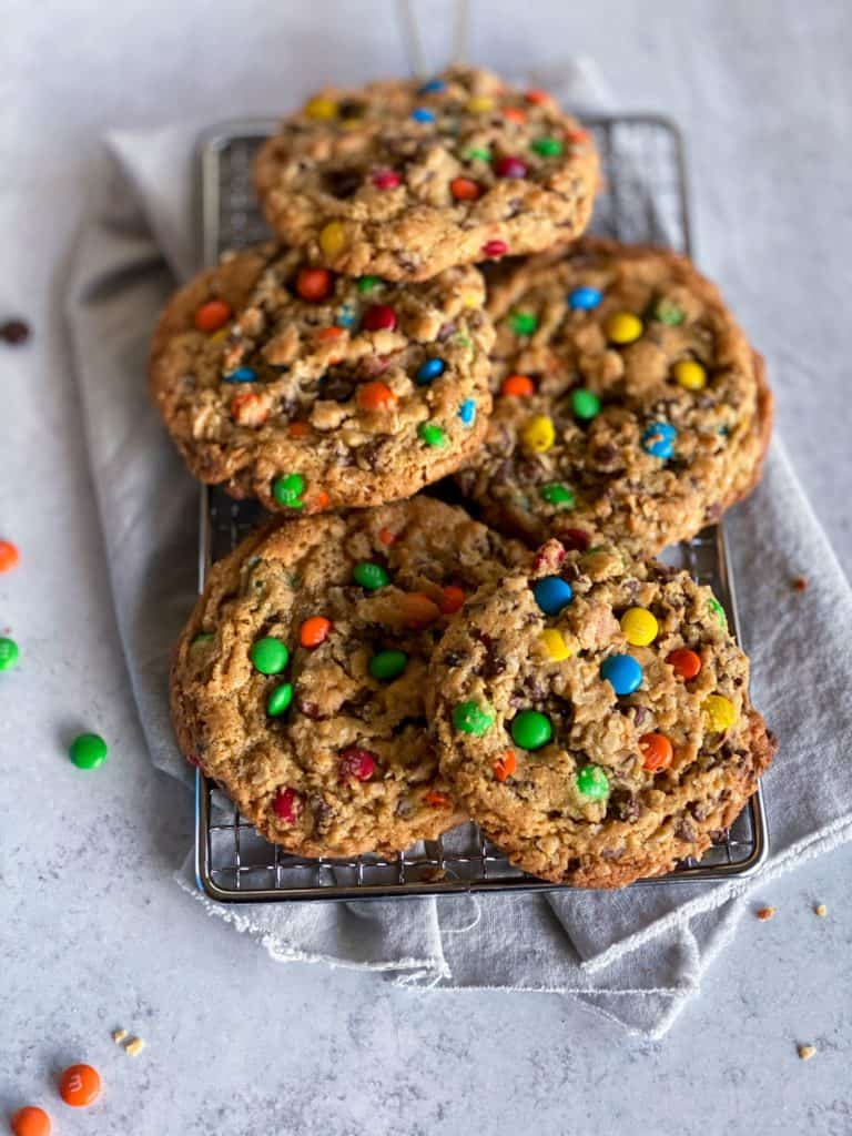 stack of chewy monster cookies on silver grate