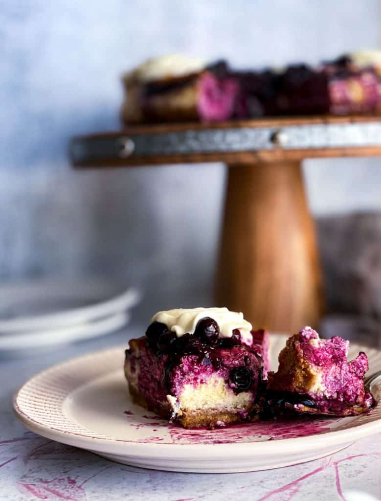a slice of blueberry cheesecake with a bite taken out