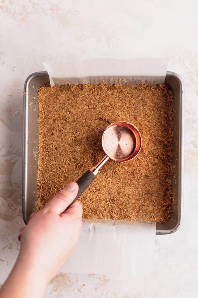 Spreading graham cracker crumbs in pan