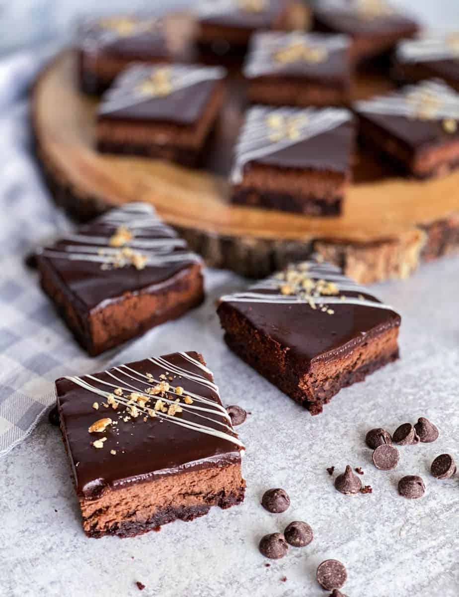 Chocolate cheesecake brownie bars laid down on a wooden platter with white chocolate drizzle and pecans on top.