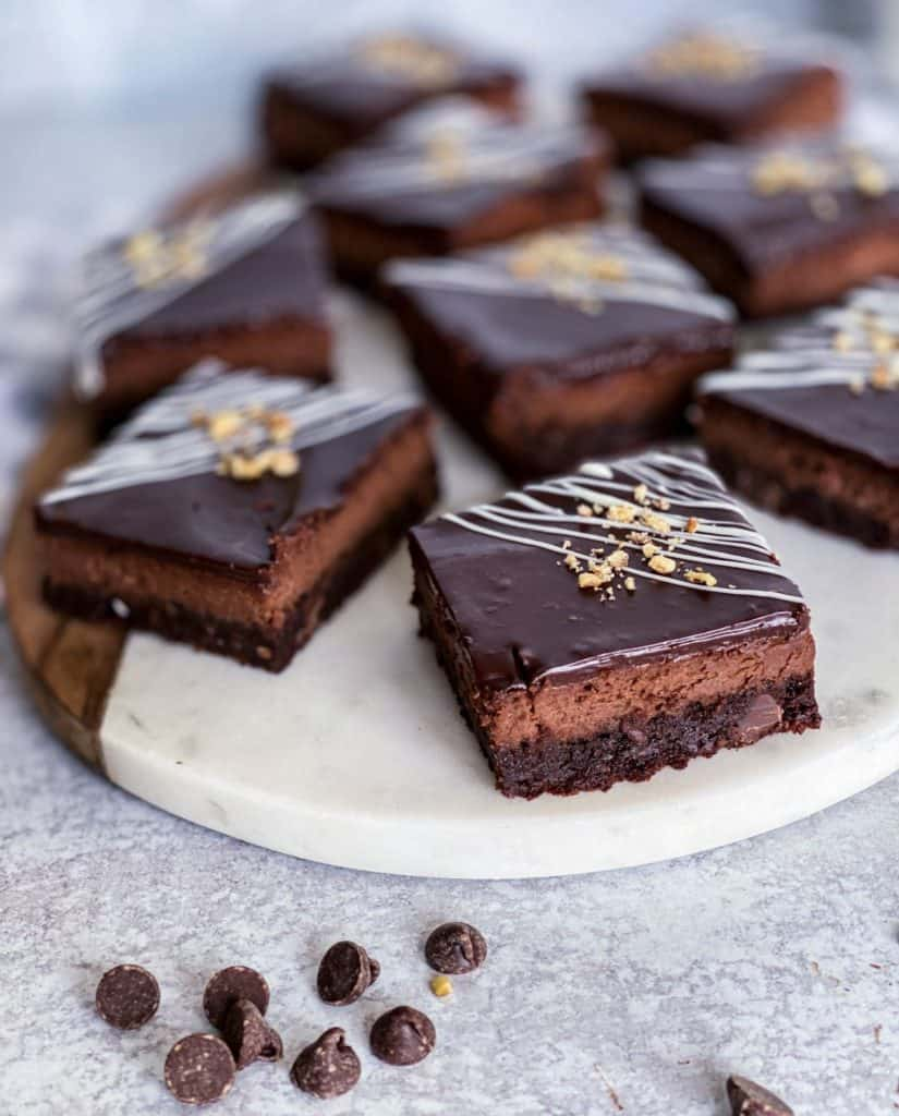 Chocolate cheesecake brownie bars on a white marble cutting board. The fudgy brownie layer is visable.