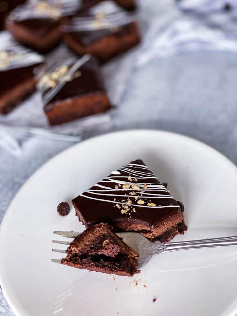 Chocolate cheesecake brownie bars with a bite taken out with a fork.