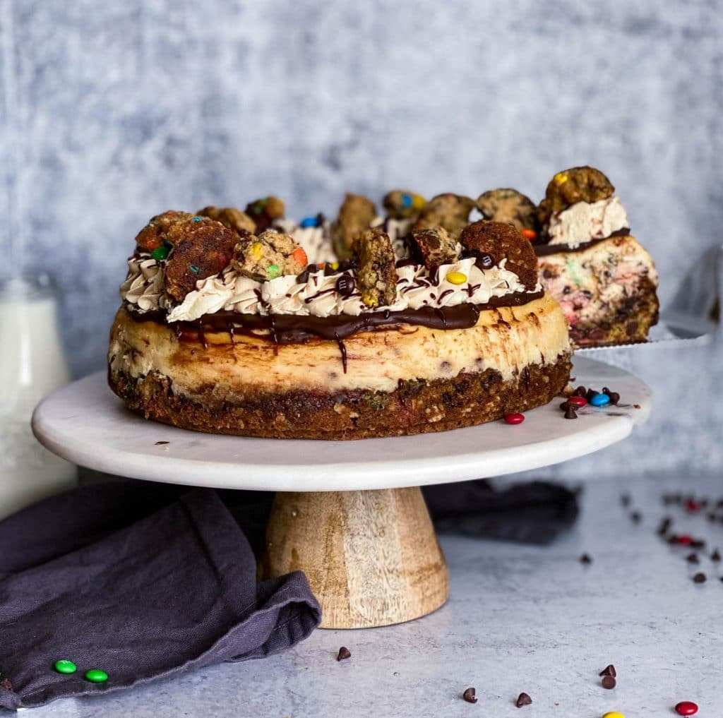 Monster cookie cheesecake on a cake stand. 1 slice is being taken out of cheesecake with mini chocolate chips scattered around.