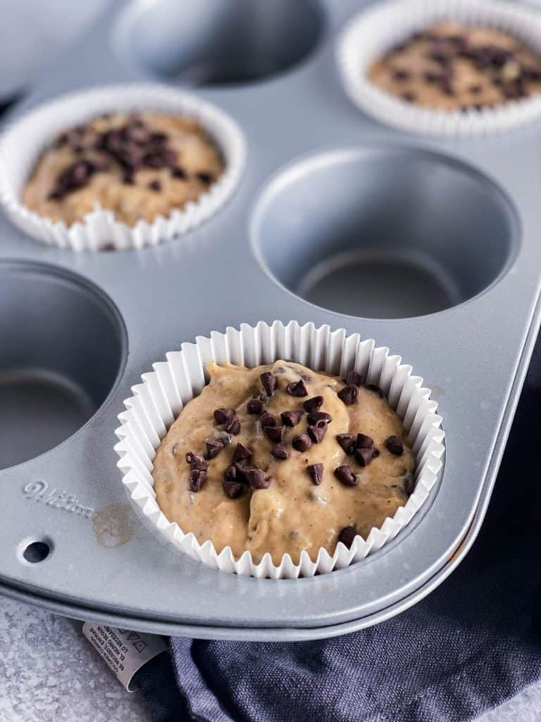 The batter of peanut butter banana muffins in the muffin tin with extra mini chocolate chips on top