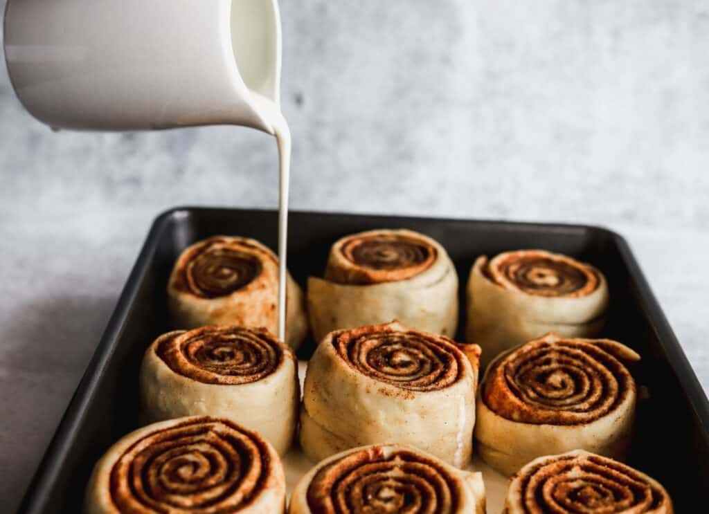 Pour heavy cream into best gooey cinnamon rolls showing off the raw dough.