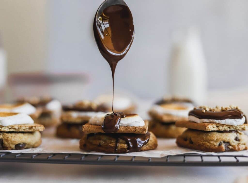 S'mores chocolate chip cookies with a drip of chocolate poured on top of a toasted marshmallow.