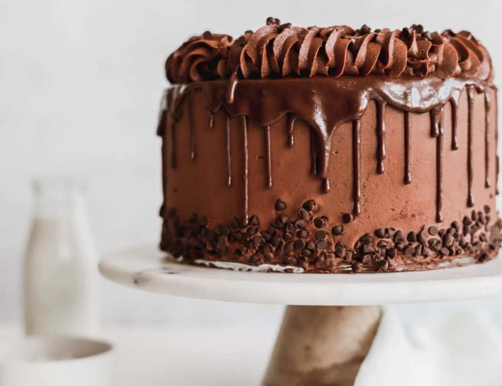Triple chocolate cake that has chocolate drizzle dripping down the sides of the cake.