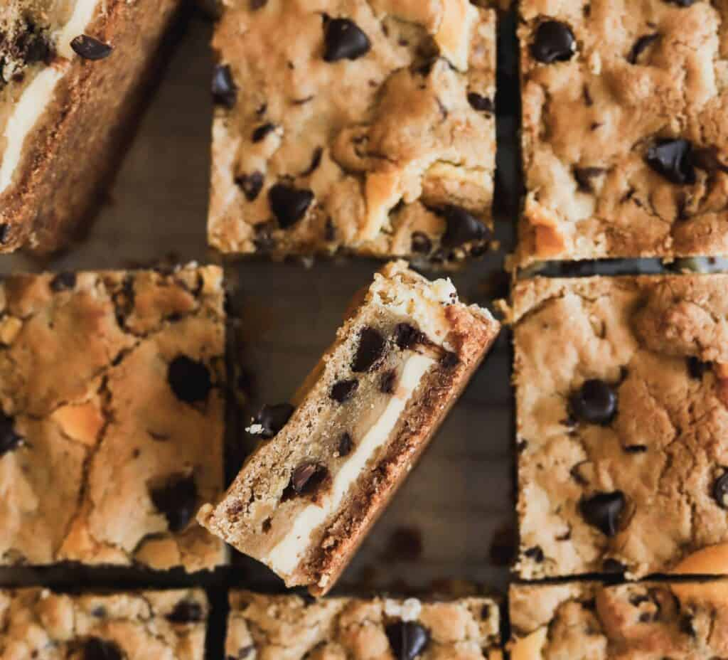 Rows of chocolate chip cookie dough cheesecake bars with one showing the cookie dough, creamy cheesecake, and graham cracker crust.