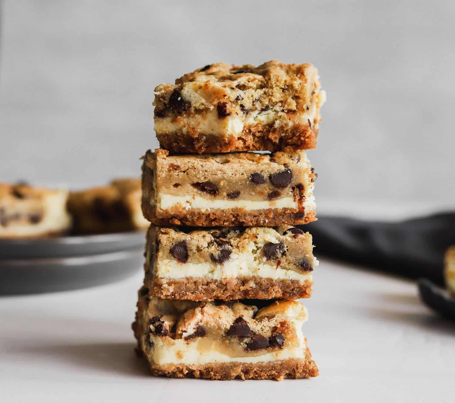 Cookie dough cheesecake bars stacked 4 tall with a bite missing.