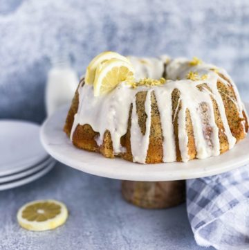 Lemon poppy seed cake sitting on a cake stand covered in cream cheese frosting.