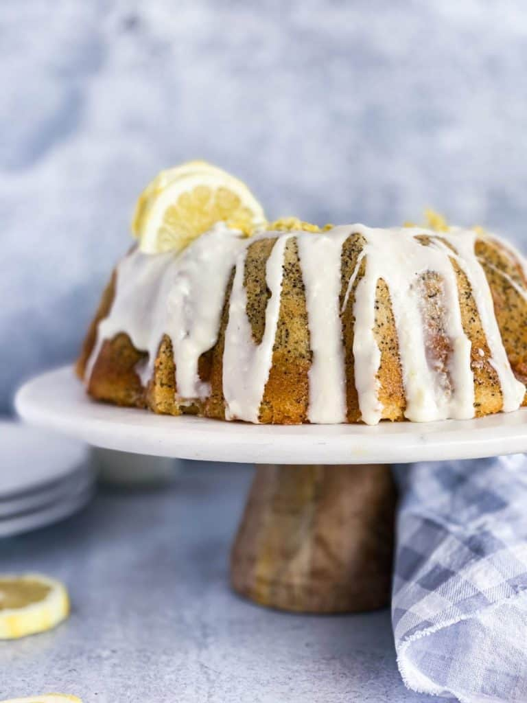 Lemon poppy seed cake on a cake stand with cream cheese frosting