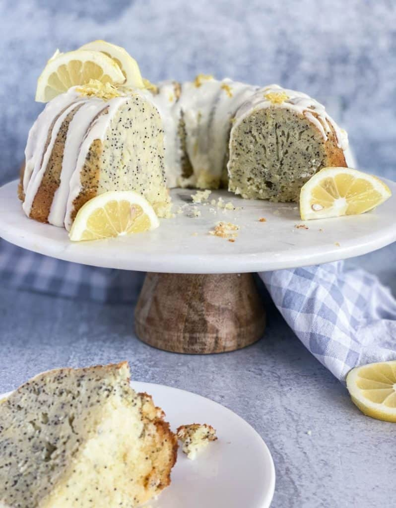 Lemon poppy seed cake as a bundt cake with pieces missing on a cake stand.