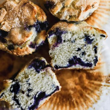 Easy homemade jumbo blueberry muffins laid on their wrapper showing the blueberry swirl.