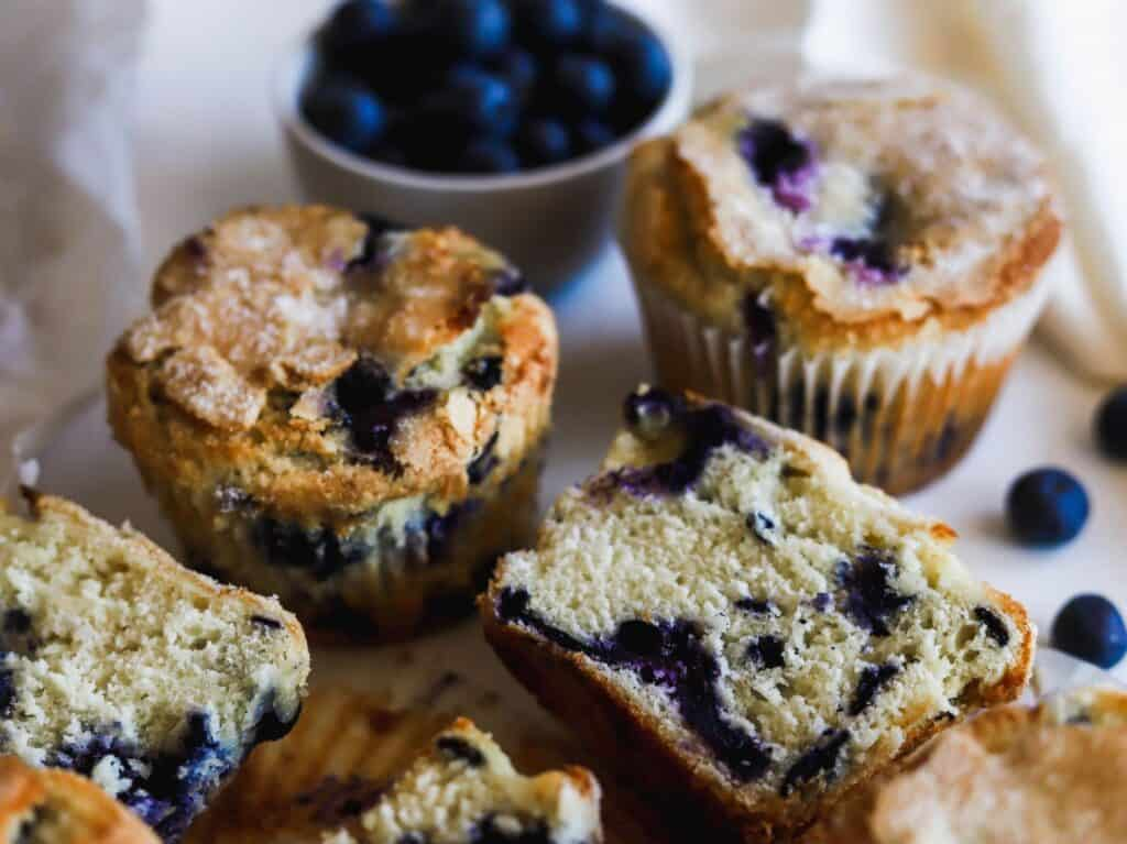 Bakery style jumbo blueberry muffins laid out to show the swirls of the blueberries.
