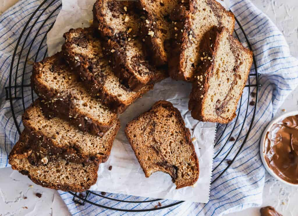 Soft and fluffy nutella swirled banana bread spread out on a cooling rack.