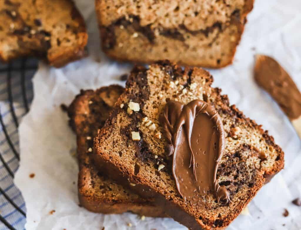 The best moist nutella swirled banana bread that has a slice cut out with more nutella on top.