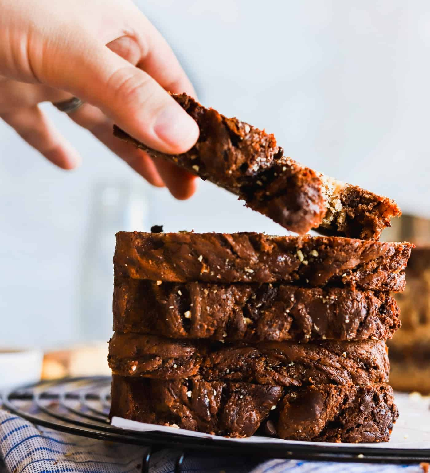 Moist Nutella swirled banana bread stack 4 high while lifting one off the stack.