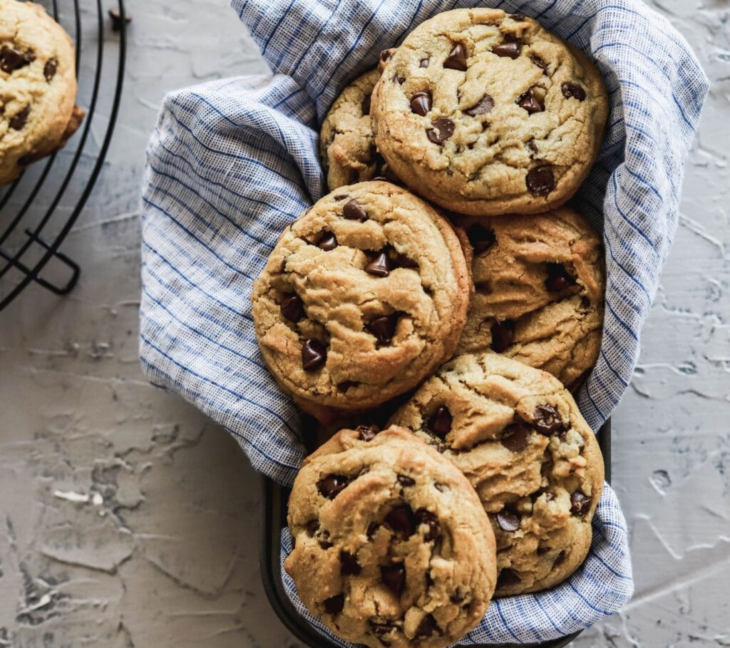 The brown butter chocolate chip cookies are large bakery style cookies in a tin with a blue napkins.