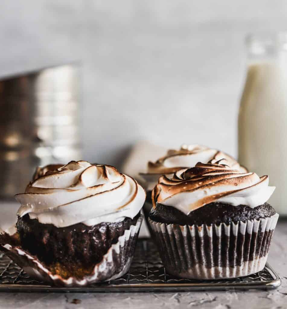 Toasted s'mores cupcakes have a graham cracker crust and a homemade marshmallow meringue and filled hot fudge