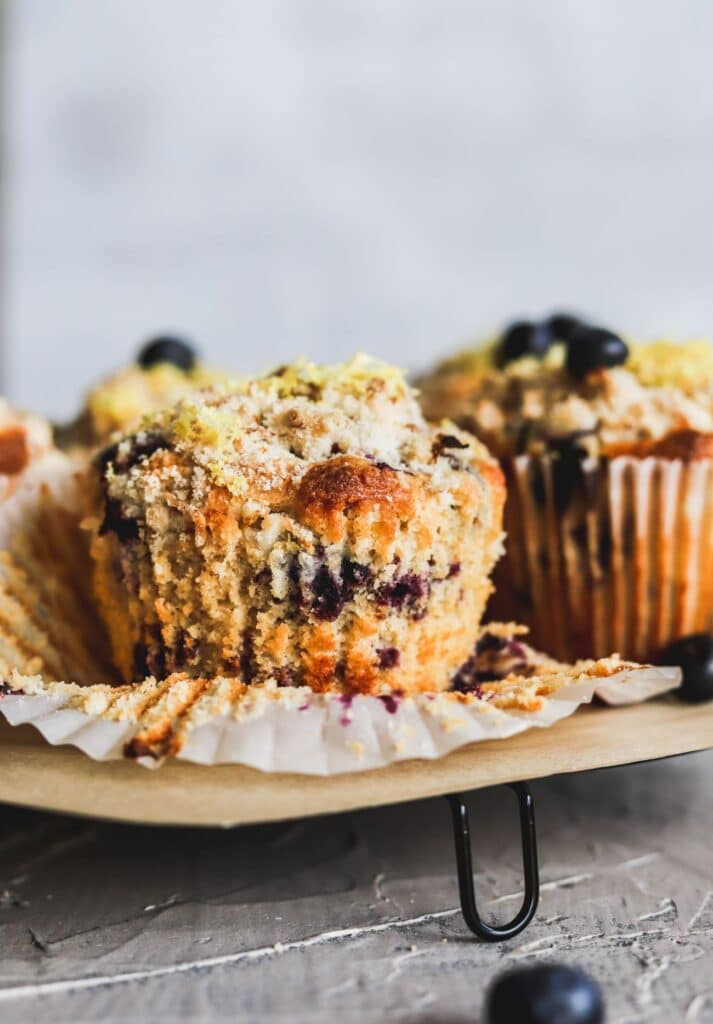 Lemon blueberry muffins with a lemon crumb topping with the muffin liners taken off.