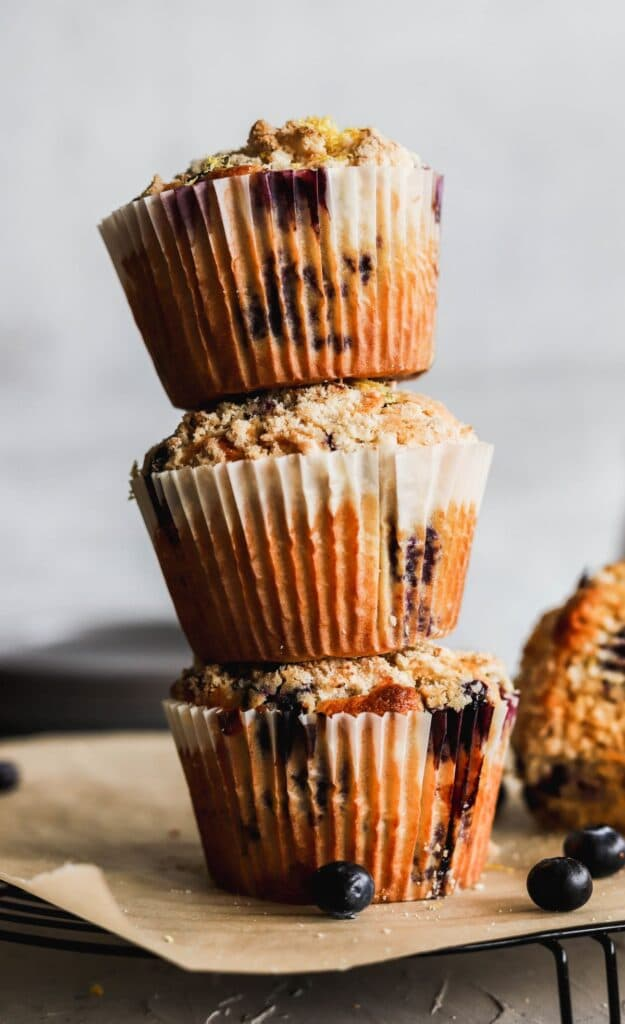 A stack of 3 jumbo lemon blueberry muffins stacked up high.