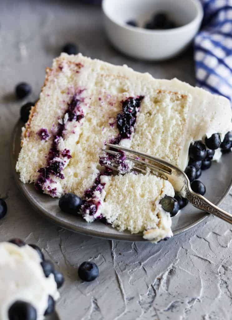 A slice of blueberry jam and cream cake with a fork inserted.