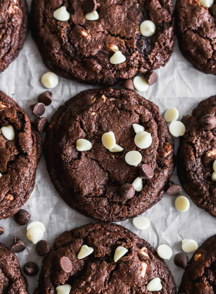 White chip double chocolate cookies laid out of parchment paper with extra chips on top.