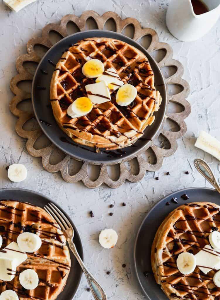 Flat lay of fluffy banana bread waffles with 3 plates of easy Belgium waffles.