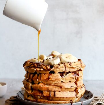 Fluffy banana bread waffles are Belgium style with lots of topping while pouring syrup