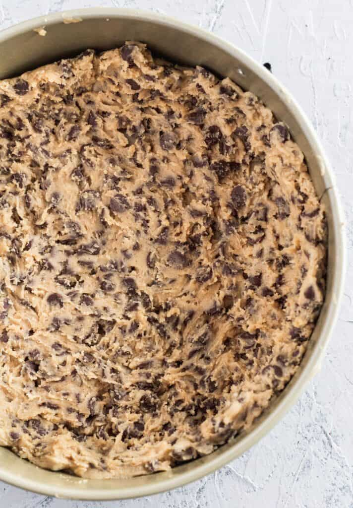 Chocolate chip cookie dough crust in a spring form pan..