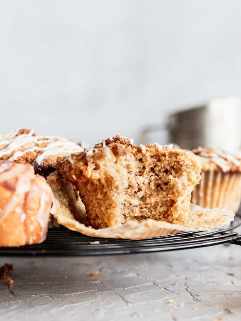 Cinnamon roll muffin with a bite taken out.