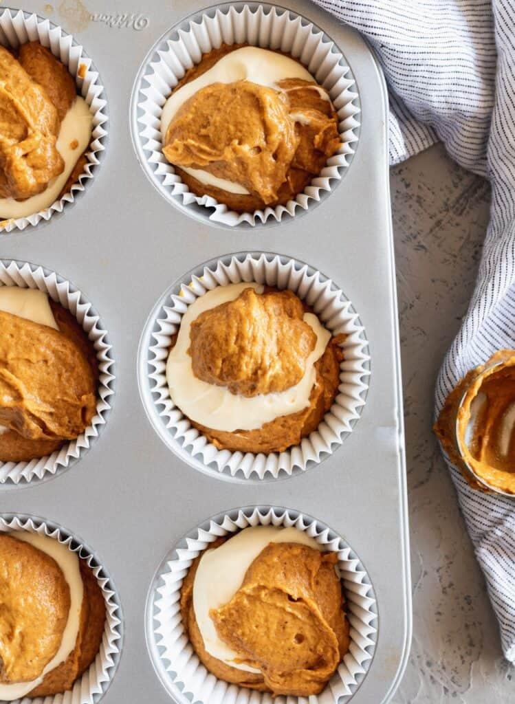 Pumpkin cheesecake muffin batter swirled together in a muffin tin.