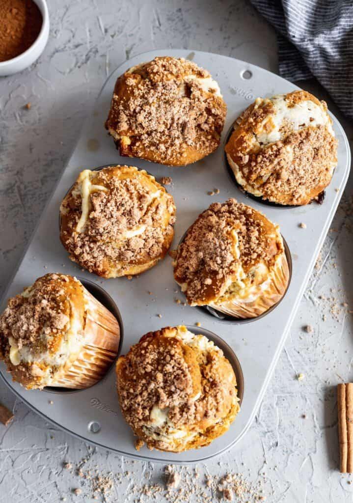 Pumpkin cheesecake swirl muffins showing off how big the jumbo muffins are.