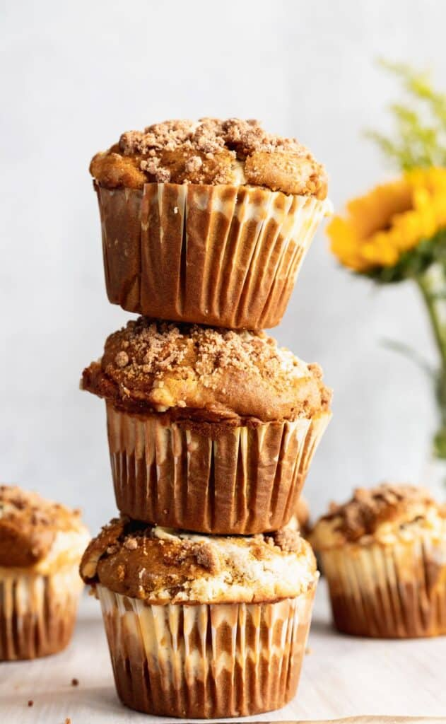 A stack of 3 pumpkin cheesecake swirl muffins stacked on top of each other.