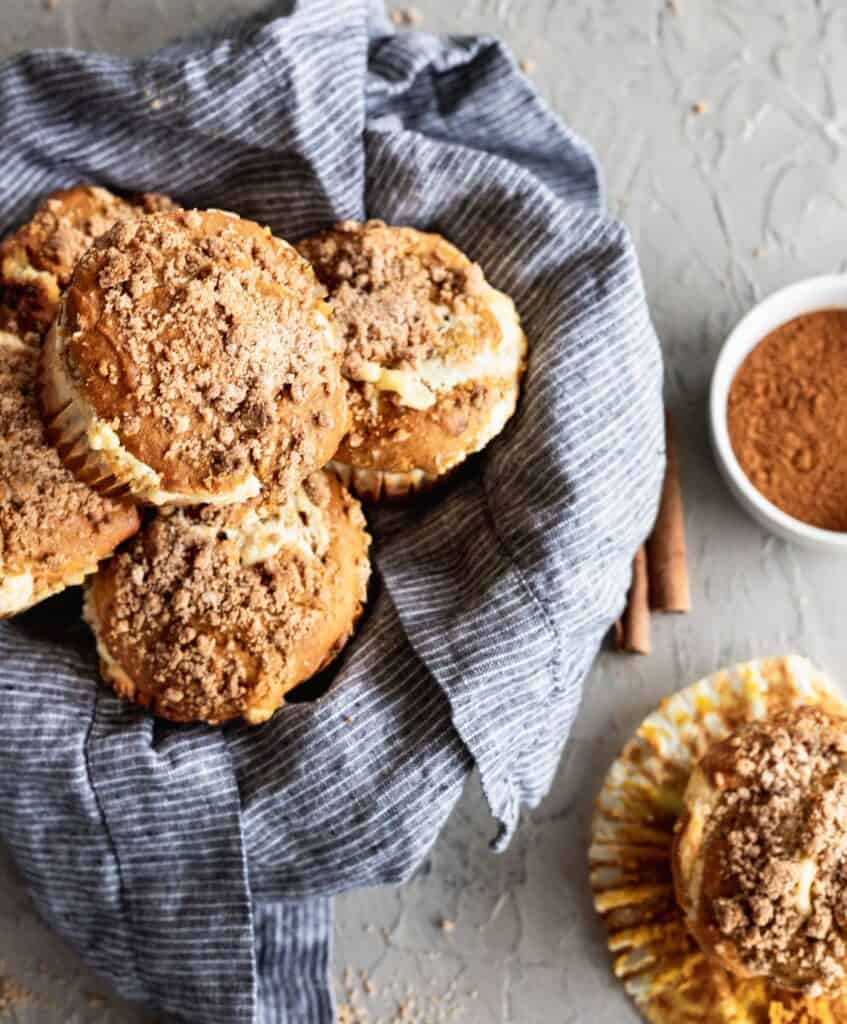 A bowl of pumpkin cheesecake swirl muffins with a cinnamon crumb topping with 1 muffin on the side.