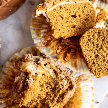 Pumpkin cheesecake muffins split in half to show off the cheesecake layer.