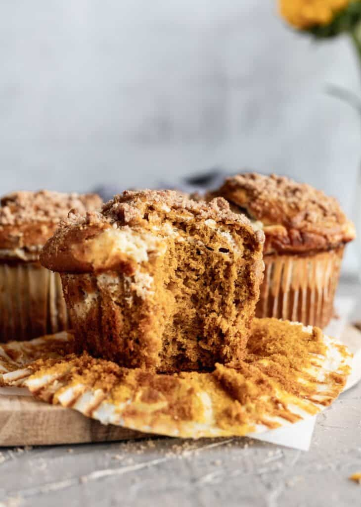 A pumpkin cheesecake swirl muffin with a big bite take out of it on a wooden board.