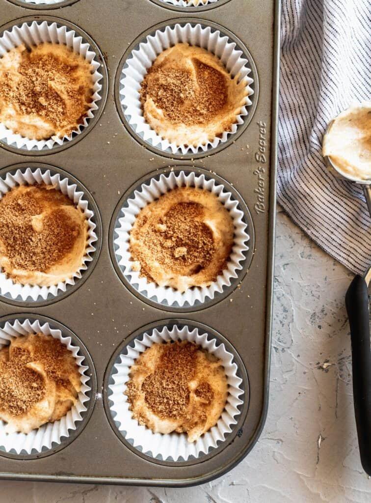 Cinnamon cupcake batter with brown sugar and cinnamon on top.