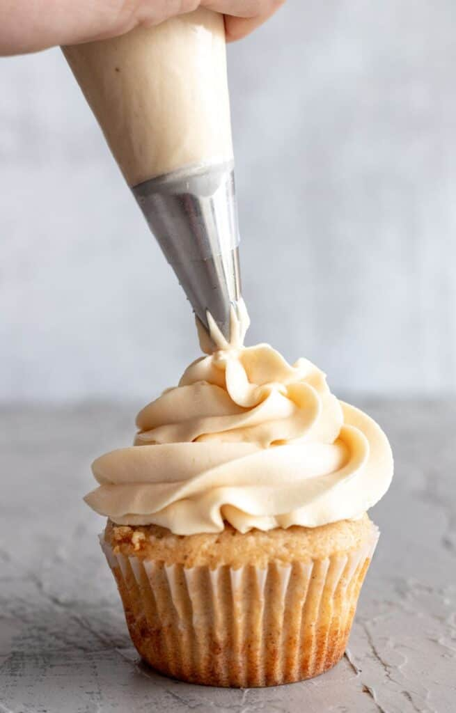 Piping salted caramel buttercream on the cinnamon cupcake