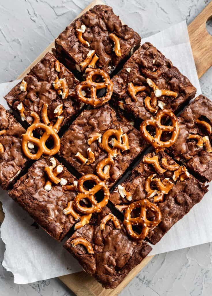 Fudgy pretzel brownies on a square cutting board.