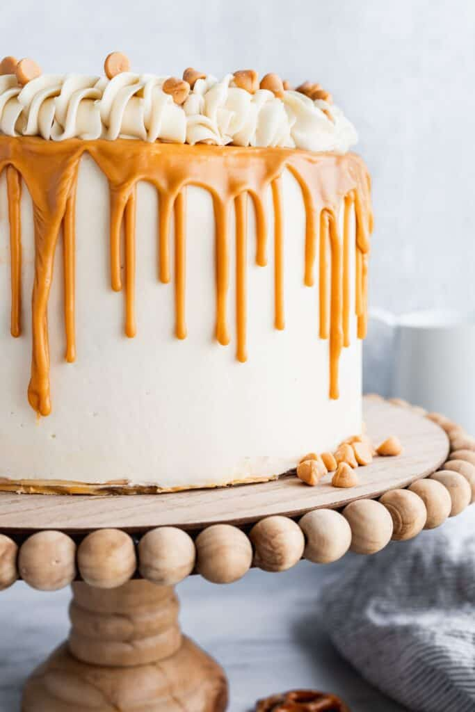 Butterscotch cake with pretzel brownies on a cake stand with a butterscotch ganache drip.