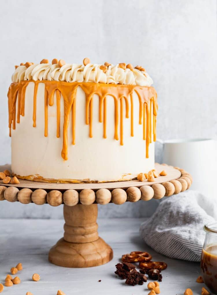 Butterscotch cake with pretzel brownies on a wood cake stand with pieces of brownies scattered.