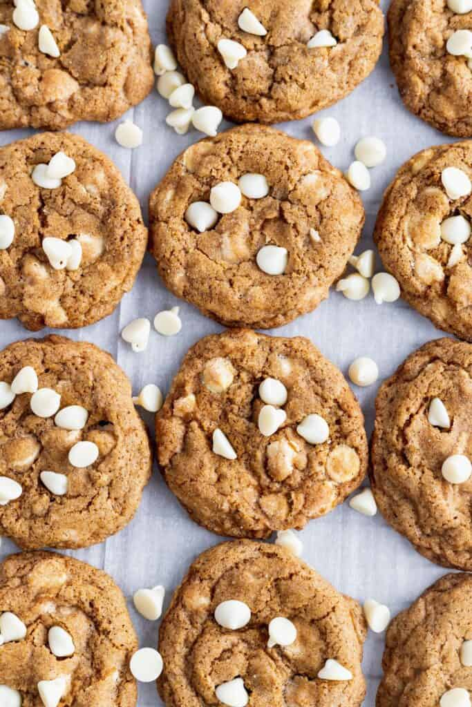 White chocolate pumpkin snickerdoodle cookies laid out with extra white chocolate chips.
