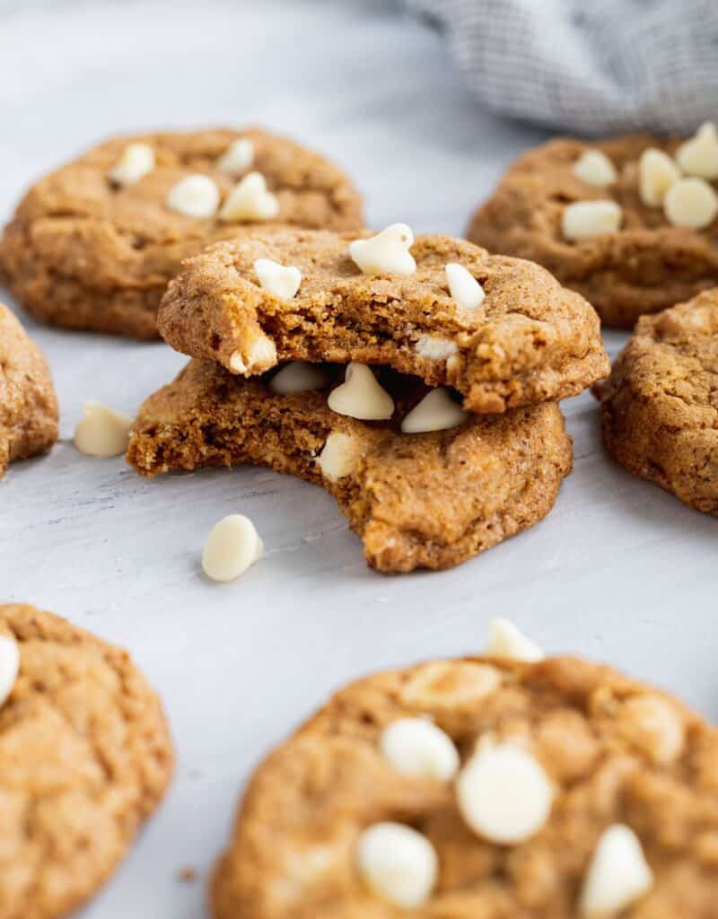 White chocolate pumpkin snickerdoodle cookies with 2 cookies stacked on top with bites taken out.