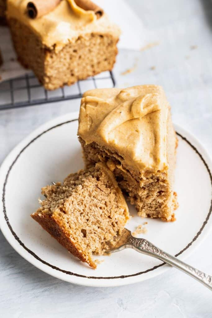 1 slice of spice sheet cake with pumpkin frosting on a plate with a bite missing.