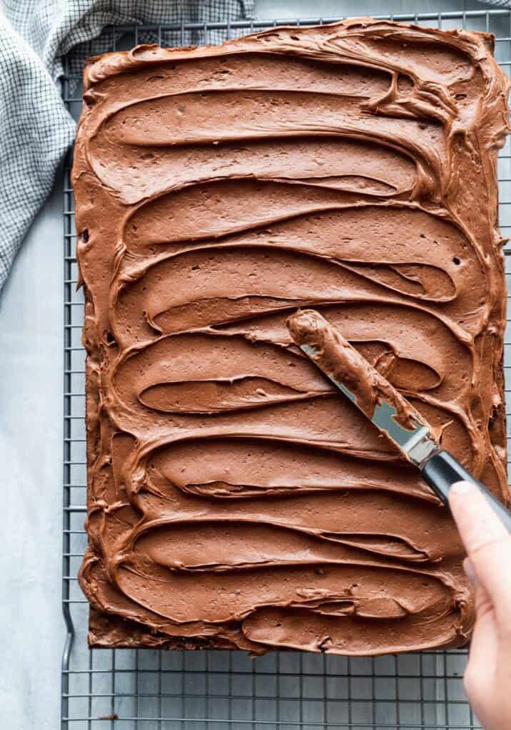 Chocolate frosting on the fudgy brownies spreading it around with a spatula.